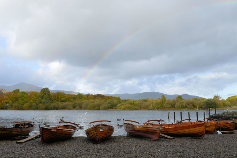 Boats moored on riverbank against rainbow in cloudy sky