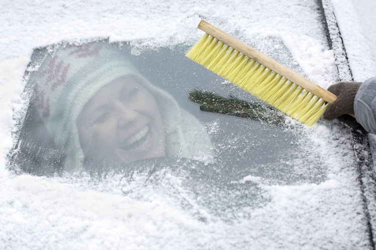 Close-up portrait of smiling woman on snow