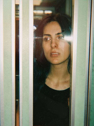 Thoughtful Young Woman Seen Through Elevator