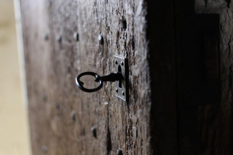 Close-up of key in lock on door