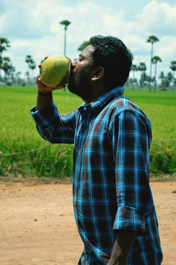 Side view of man drinking coconut water while standing on footpath by grassy field
