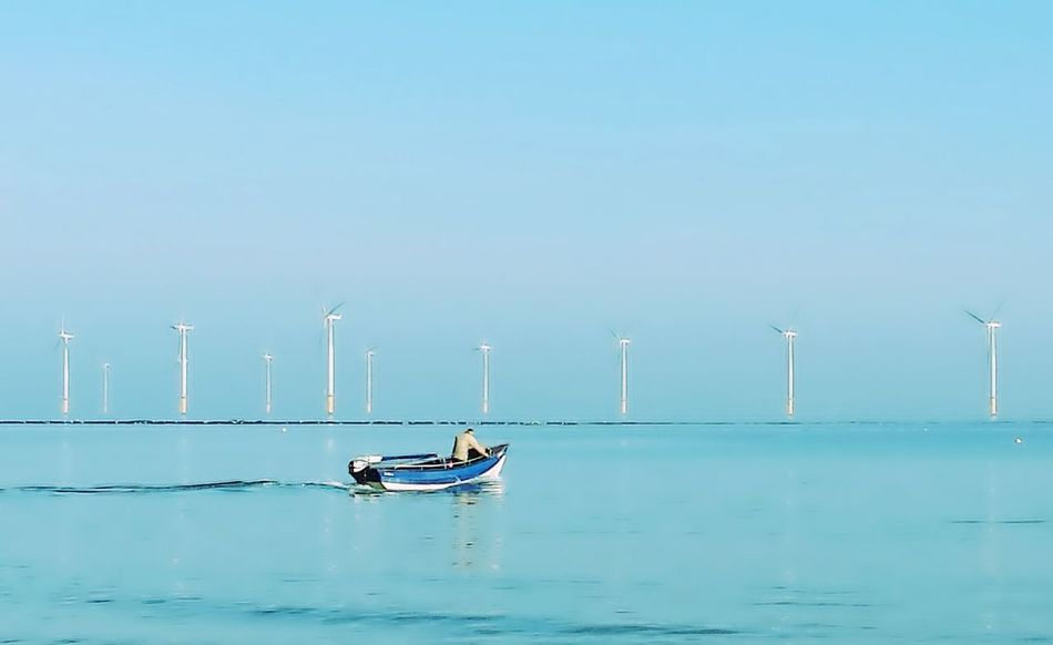 Blue Sea Water Nautical Vessel Clear Sky Environment Horizon Over Water Nature Transportation Sky Outdoors Floating On Water Beauty In Nature Tranquility Man And Boat Wind Turbines Fisherman Boat Clinker Built Boat Fishing Boats EyeEm Best Shots Seascape Sea And Sky Scenics Sailing The Great Outdoors - 2017 EyeEm Awards
