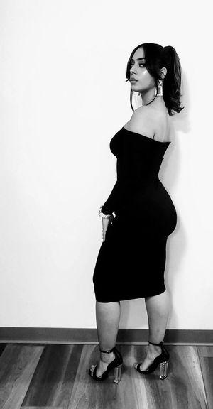Full length of woman standing on hardwood floor against wall