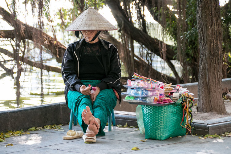 Streetphotography Street Photography Culture Vietnamese Hat Woman One Person Real People Hat Full Length Front View Sitting Clothing Casual Clothing Lifestyles Adult Tree Leisure Activity Seat Outdoors Nature Plant Vietnam Hanoi Working Working Woman