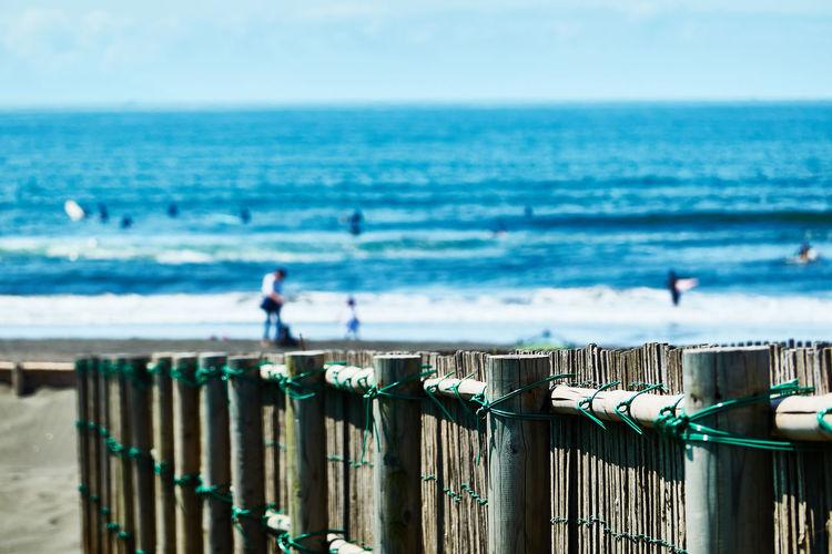 Wooden fence on beach against sky