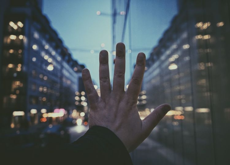 Midsection of hand in city at night