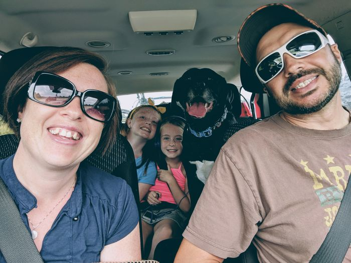 Portrait of cheerful family with dog in car