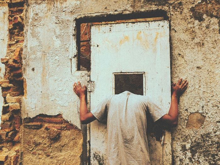 Rear view of person standing against door