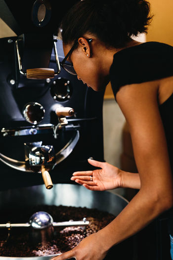 Side view of woman grinding coffee beans