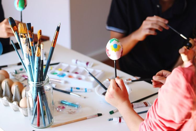 Children Painting Eggshells At Table