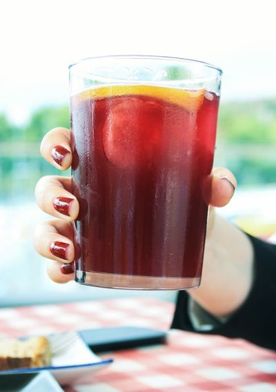 Close-up of cropped woman hand holding drink at restaurant