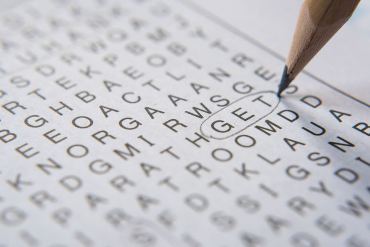 Close-up of pencil marking get text on puzzle