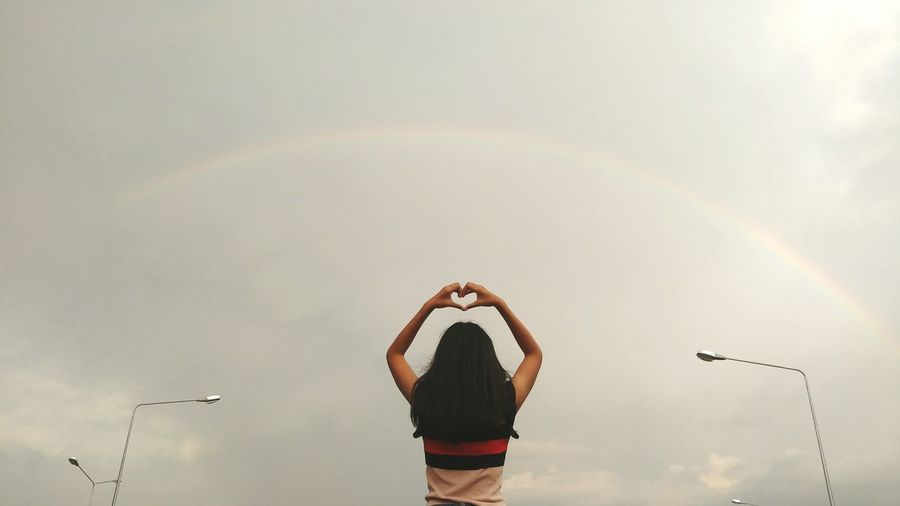 Low angle view of woman making heart shape while standing against rainbow in cloudy sky