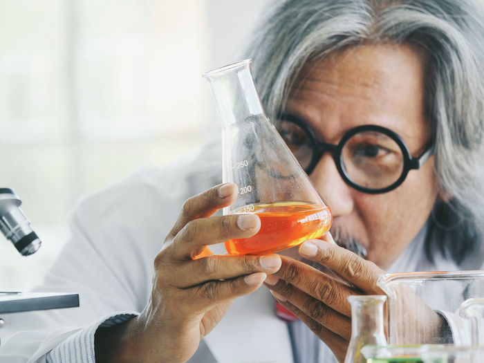 Indoors  Holding Headshot Portrait Front View Refreshment Adult Eyeglasses  Glass Focus On Foreground Drink Healthcare And Medicine Real People Food And Drink People Mature Adult Close-up Transparent Glasses Orange