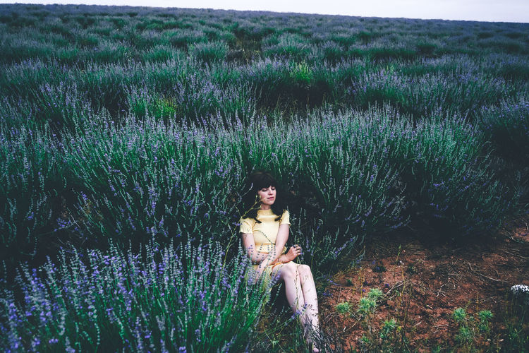 Young woman sitting on field by plants