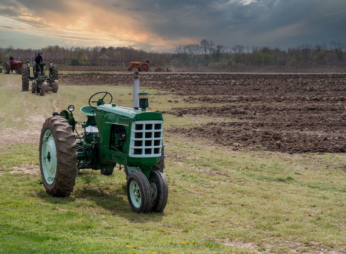 Tractors plowing a springtime field at sunset