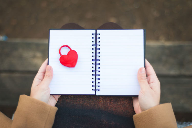 Close-up of hands holding heart shape padlock in notebook