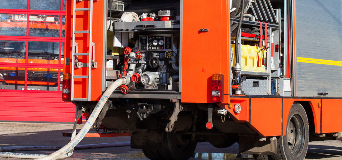 Fire engine in action with connected fire hose Backside Fire Engine Fire Engines Firefighter Rear View Active Activity Car Connecting Connection Equipment Fire Brigade Fire Truck Fireman Germany Interior No People Operating Outdoors Parking Professional Red Rescue Water Hose