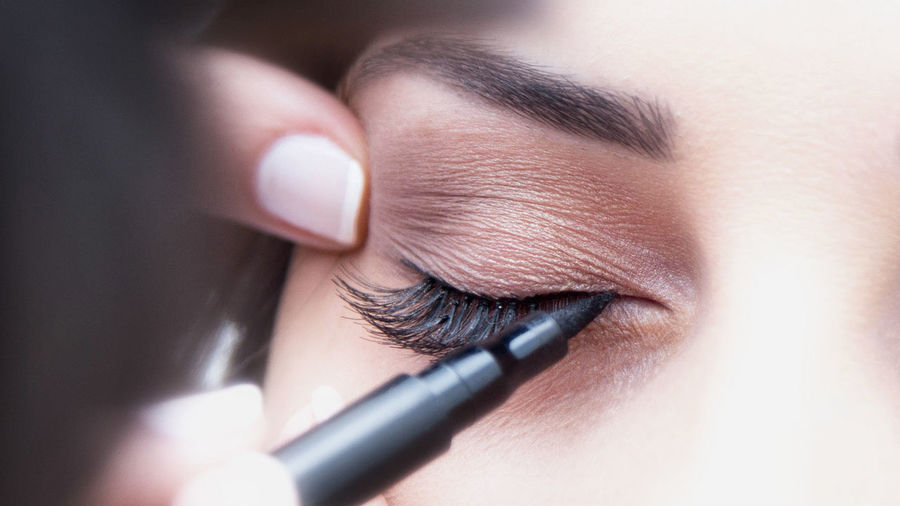 Close-Up Of Cropped Make-Up Artist Applying Eyeliner On Woman