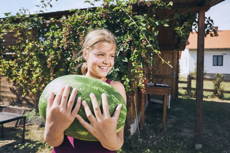 Cheerful Girl Holding Watermelon While Standing In Yard