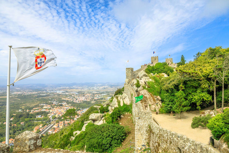 Aerial view of ancient wall and tower of Castle of the Moors and Sintra valley. Castelo dos Mouros is medieval castle and Unesco Heritage on a hill above Sintra, Lisbon District, Portugal. Pena Palace and the ruins of Moors Castle are popular landmarks and major tourist attractions of the Cultural Landscape of Sintra as a World Heritage Site, Portugal. Portugal Sintra Castle Ruins Medioeval Cities Wall Tourism Flags Skyline Cityscape Palace Castle Ruin Aerial View Moors Castle Pena Palace Moors Architecture Tree Sky Built Structure Building Exterior Plant Cloud - Sky Flag Nature Building Patriotism Day City History No People The Past Travel Travel Destinations Landscape Outdoors Stone Wall