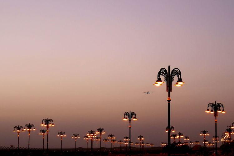 Illuminated street lights against clear sky