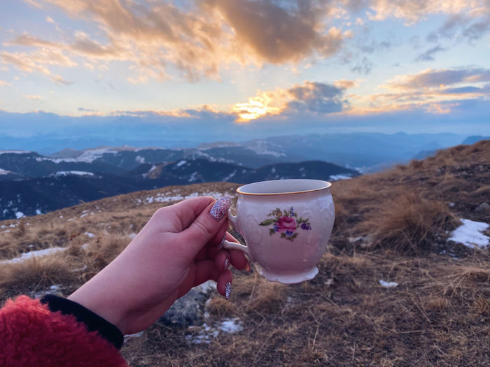 Midsection of person holding ice cream against mountains during sunset