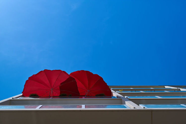 Directly below shot of red umbrella against blue sky