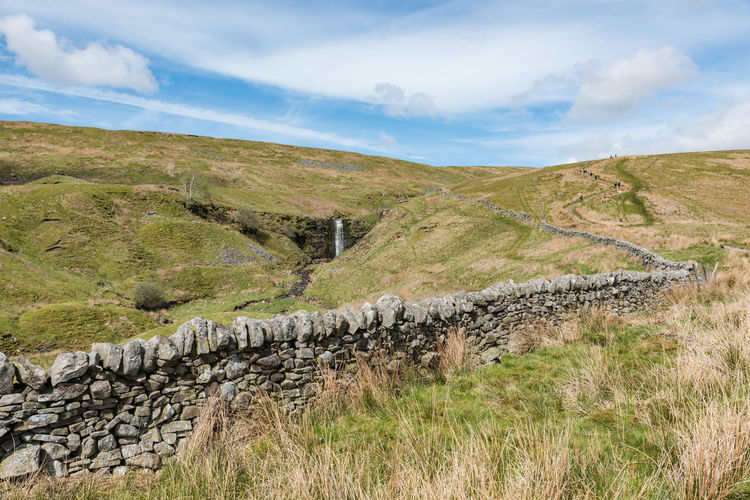 An ascent to the whernside peak with a waterfall in the distance, yorkshire three peaks challenge