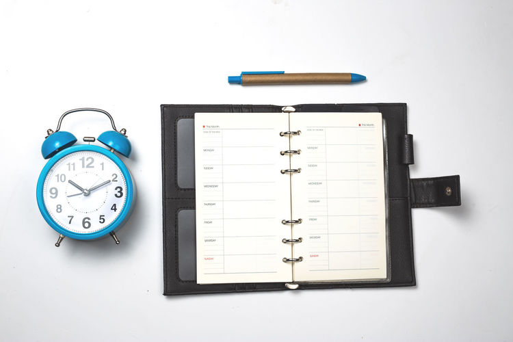 Still Life Indoors  Time Clock White Background No People Studio Shot Publication Alarm Clock Book Cut Out Blue Table Accuracy Communication Close-up Pencil Technology High Angle View Education