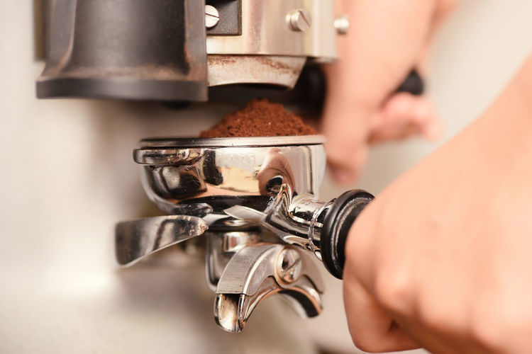 Close-Up Of Hand Making Coffee
