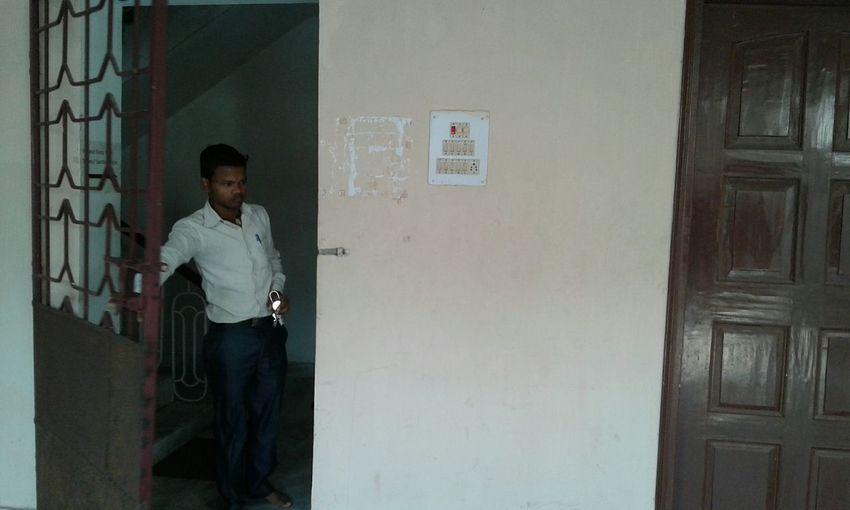 Young man standing by metallic door