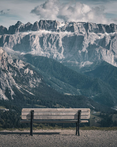 Empty bench on snowcapped mountains against sky
