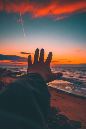 Cropped of hand against sea during sunset