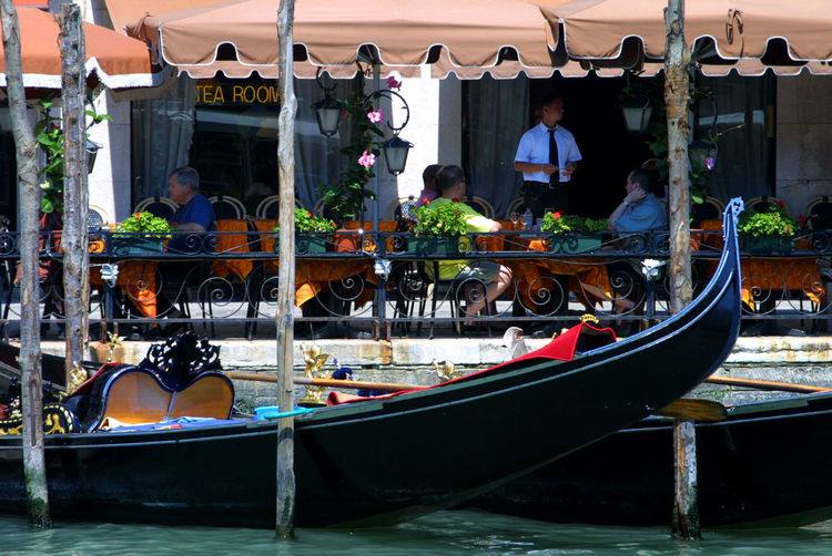 Venetian gondolas moored next to a riverside bar - Grand Canal, Venice, Ital Gondolas Venice Architecture Building Exterior Built Structure Day Leisure Activity Lifestyles Men Mode Of Transport Nautical Vessel Occupation Outdoors Real People Transportation Venice Bar Water Women