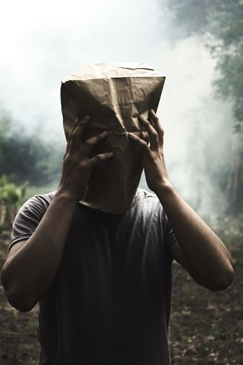 Man wearing paper bag while standing in forest