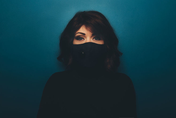 Portrait of woman wearing mask against colored background