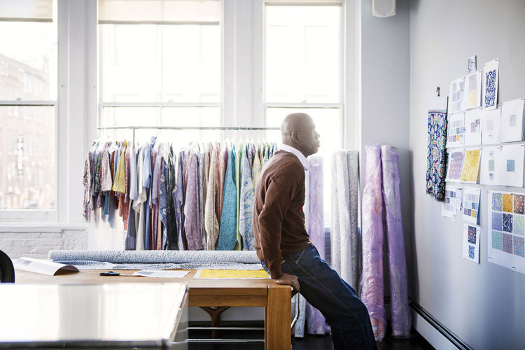 Side view of male fashion designer looking at designs on wall in workshop
