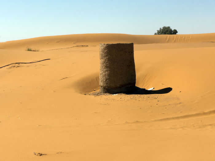 A well shaft in the Sahara desert in the south of Morocco. Behind the sand dune a shrub can be seen Sand Sky Land Desert Sand Dune Arid Climate Landscape Scenics - Nature Climate Nature Environment Tranquil Scene Tranquility Clear Sky Non-urban Scene Remote No People Day Sunlight Horizon Over Land Outdoors Morocco Sahara Well  Shaft Water Hot Shrub