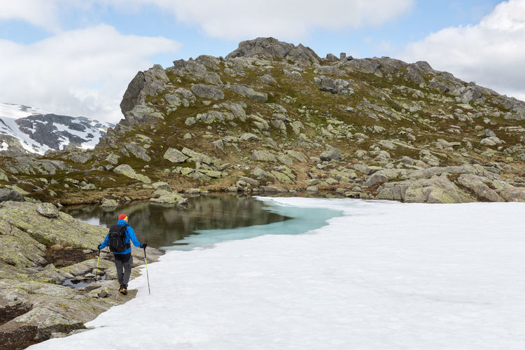 Rear View Of Person Hiking By Frozen Lake