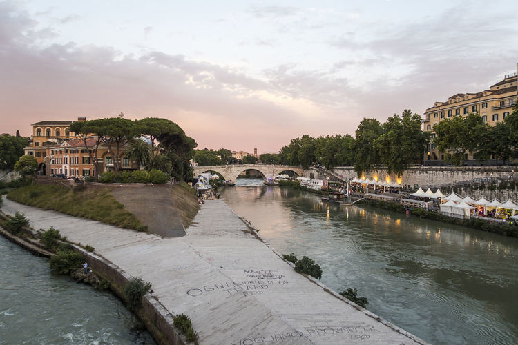 Bridge over river at tiber island against sky during sunset