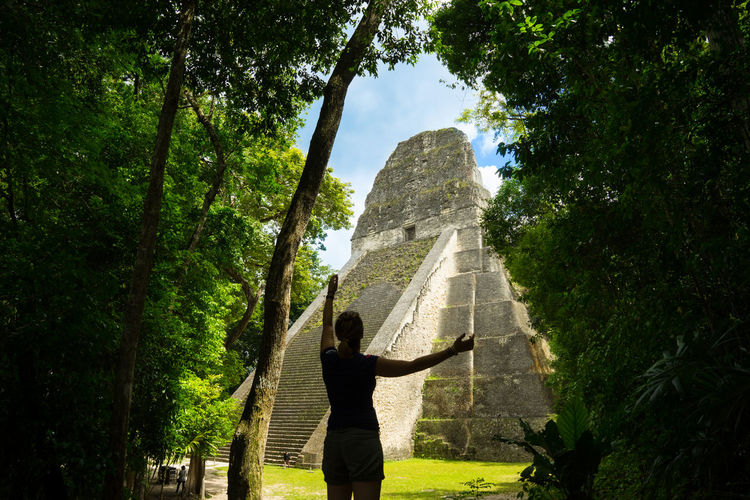 Rear View Of Woman Standing Against Old Ruins Amidst Trees