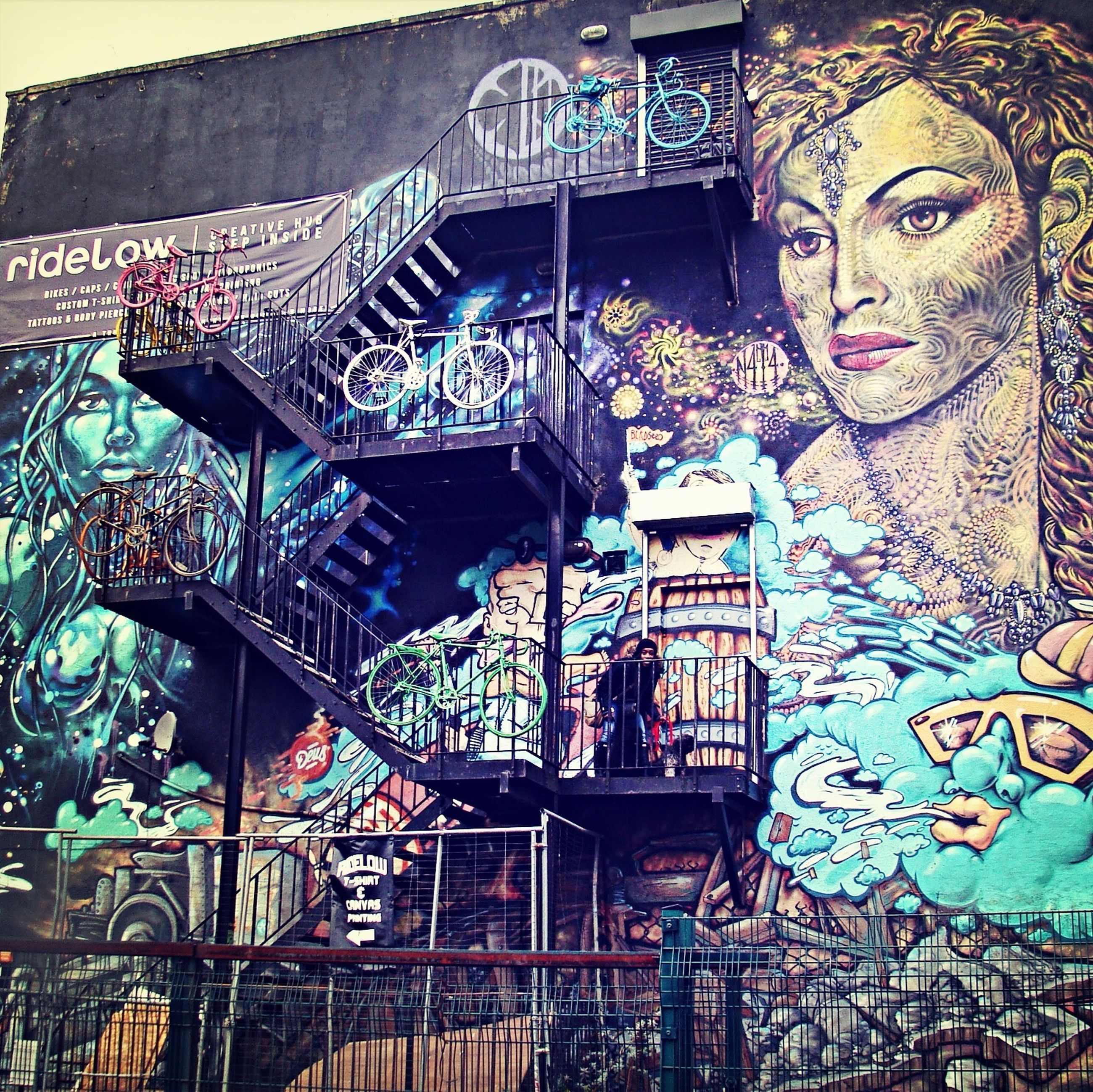 architecture, built structure, building exterior, art, art and craft, graffiti, creativity, low angle view, wall - building feature, building, design, human representation, mural, pattern, day, railing, multi colored, outdoors, steps