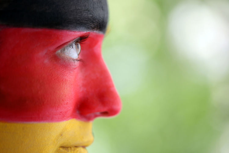 A football fan with a painted face (colors of Germany). Close-up Flag Focus On Foreground Football Fan Football Fans Football Fever German Germany Headshot Human Face Looking Away Multi Colored Multicolors  Outdoors Painting Painting Artwork Portrait Soccer The Color Of Sport