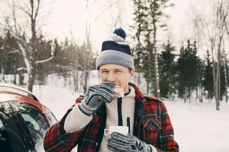 Full length of young man wearing hat against trees during winter