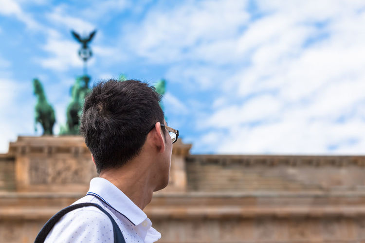 Side view of man looking away against sky in city