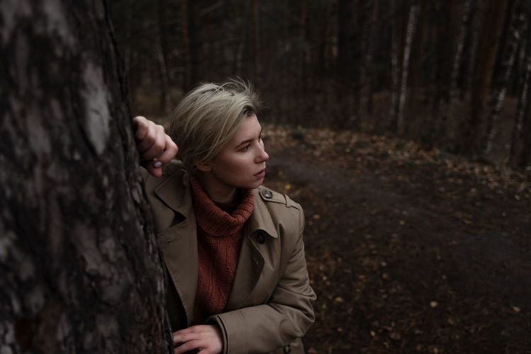 Young woman standing by tree trunk in forest