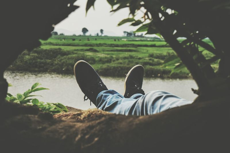Low section of man relaxing at riverbank