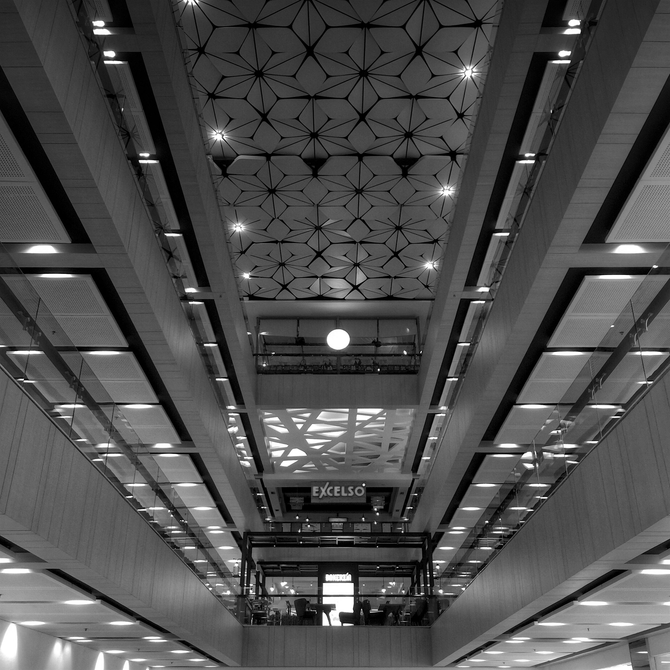 indoors, ceiling, architecture, built structure, illuminated, lighting equipment, low angle view, railroad station, modern, transportation building - type of building, in a row, shopping mall, diminishing perspective, incidental people, subway station, transportation, public transportation, interior, rail transportation, no people