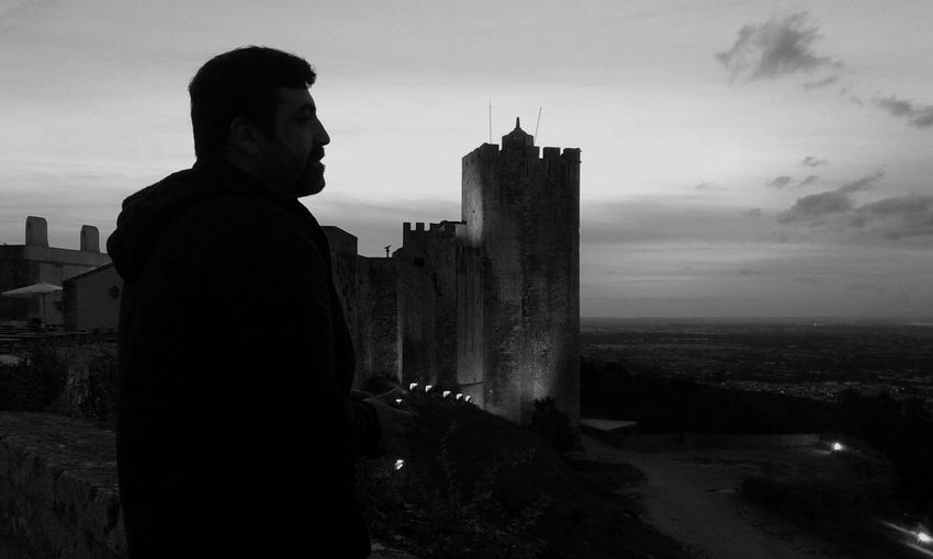 Man standing by historic castle against sky